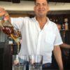 Einheimischer Kubaner gießt Rum ins Glas in einer Strandbar am Strand von Cayo Jutías auf Kuba - Gruppenreisen für Alleinreisende & Erlebnisreisen | QUERIDO MUNDO