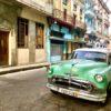 Grüner Oldtimer vor einer farbenfrohen Häuserkulisse im Centro Havannas auf Kuba - Gruppenreisen für Alleinreisende & Erlebnisreisen | QUERIDO MUNDO