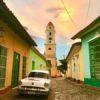 Oldtimer, bunte Kolonialhäuser & Kirchturm beim Sonnenuntergang in Trinidad auf Kuba - Gruppenreisen für Alleinreisende & Erlebnisreisen | QUERIDO MUNDO